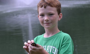 young boy holds small animal by pond
